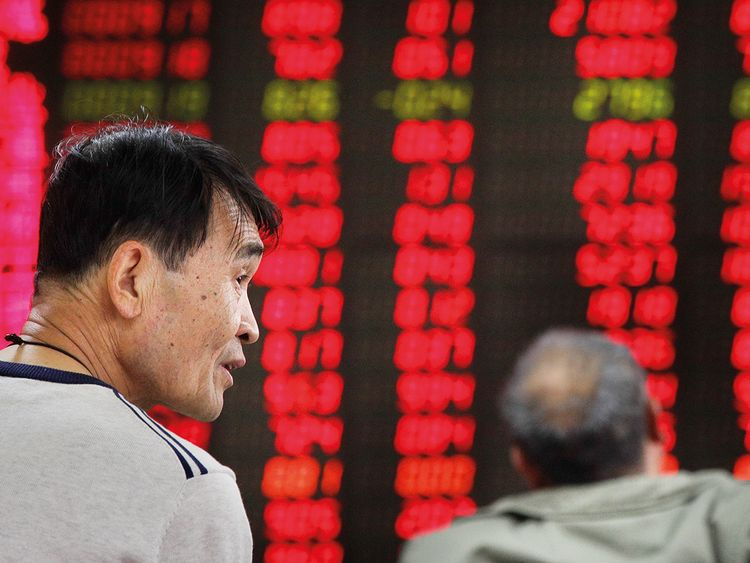 Investors monitor stock prices at a brokerage house in Beijing