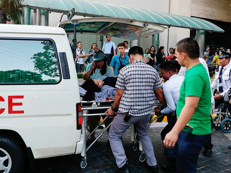 Rescue workers carry a woman to an ambulance