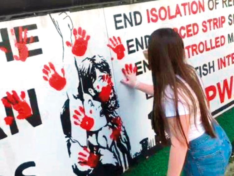 A number of women smear red paint in hand prints