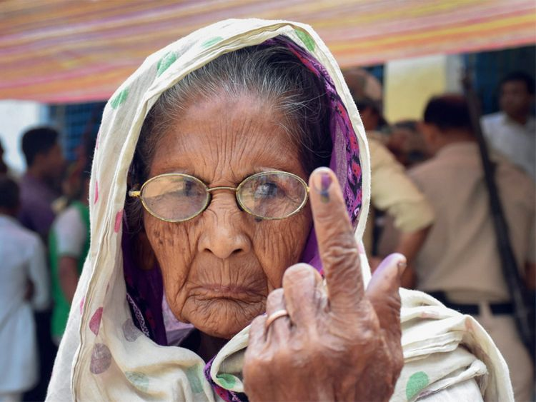 An elderly woman shows her inked marked finger