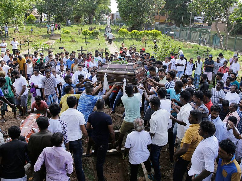 Sri Lankans prepare to bury the coffins carrying remains of people