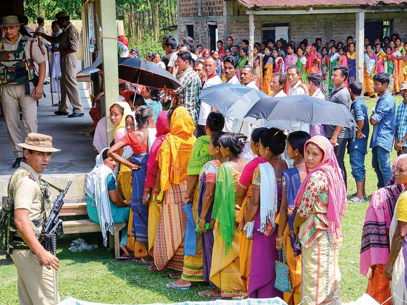 Voters stand in a queue to cast their vote