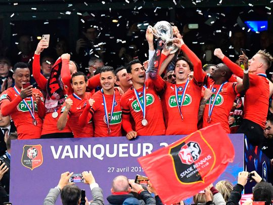 Rennes' players celebrate with the trophy