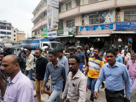 People cross a street in central Colombo