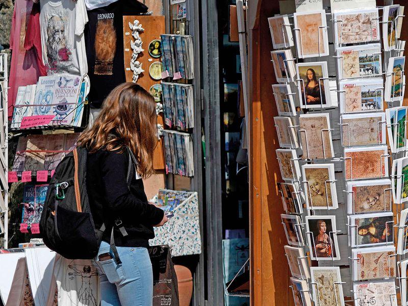 A tourist looks at a souvenirs shop in Vinci