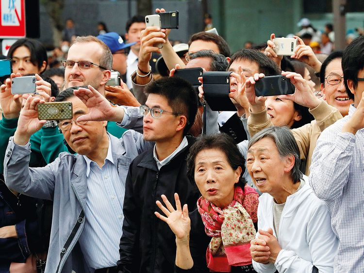 People take pictures as the Japanese royal family