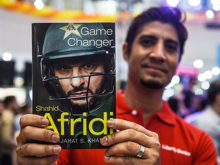 A cricket fan holds Shahid Afridi's autobiography