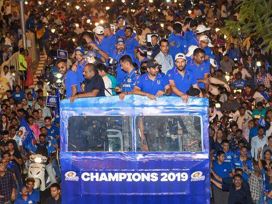 Mumbai Indians (MI) players travel atop an open bus