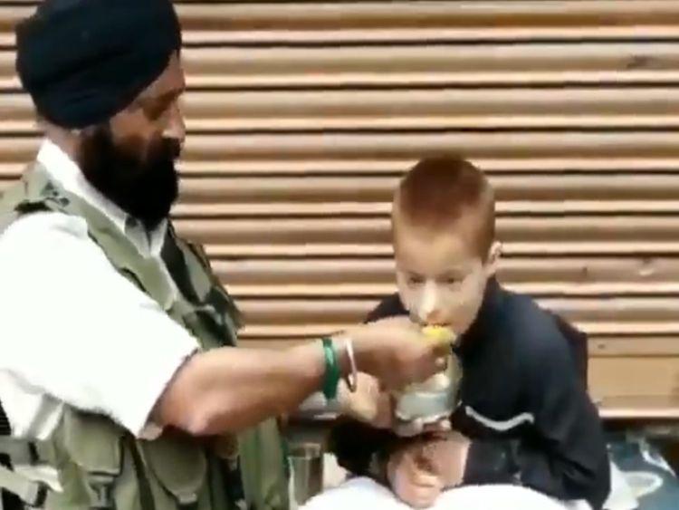 RDS_190514 Cop feeding boy-1557814216083