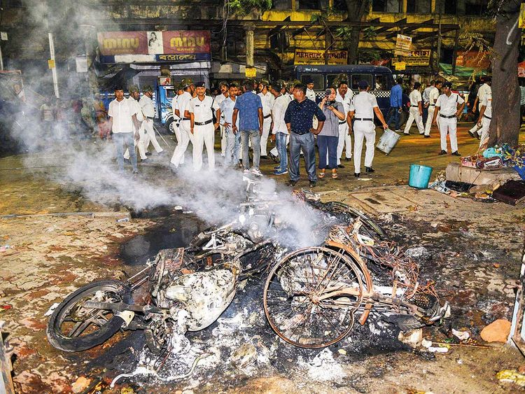 Police personnel look on near vehicles burnt by a mob
