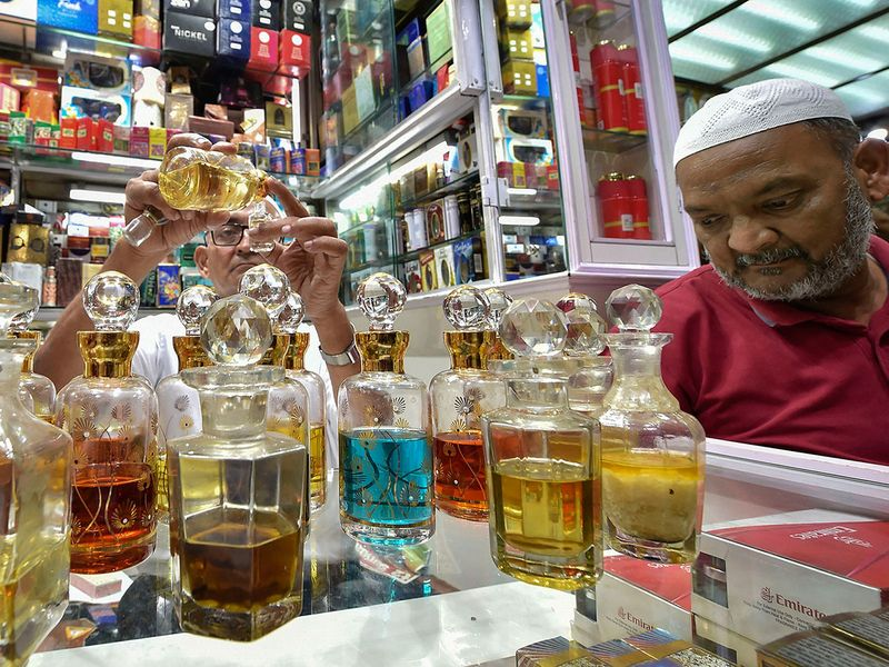 A perfume seller bottles perfumes