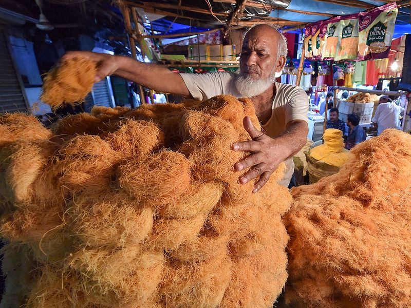 A shopkeeper arranges vermicelli