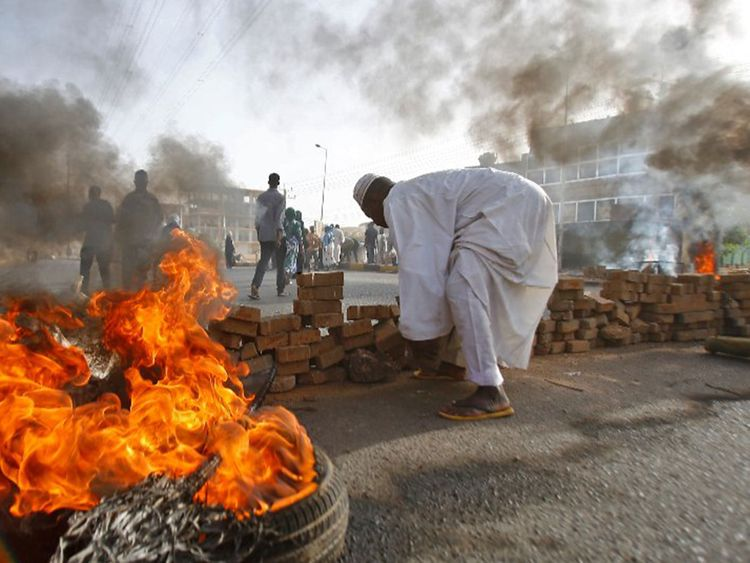 Sudanese protesters block a street with burning tires