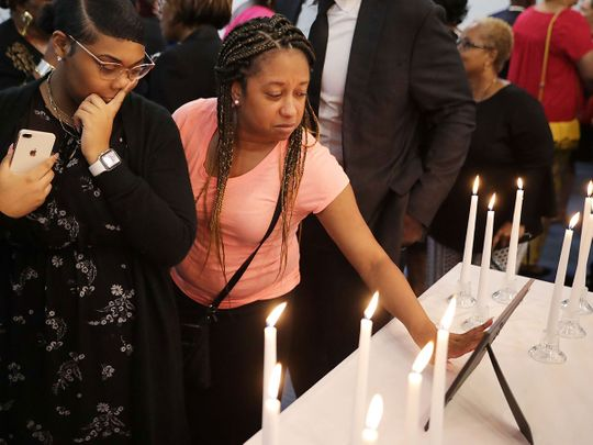mass shooting surrounded by 12 candles during a memorial service at Piney Grove Baptist Church