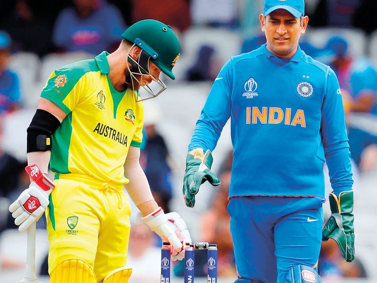 Australia's David Warner (C) and India's Mahendra Singh Dhoni