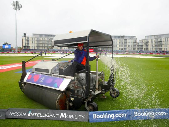 Ground staff clear water from the pitch