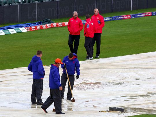 Umpires inspect the pitch