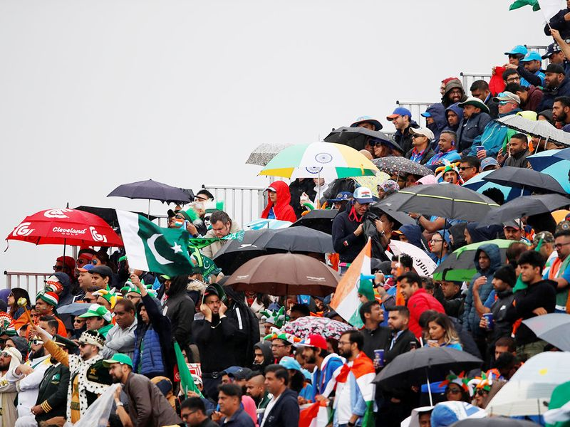Fans with umbrellas at Old Trafford as it starts to rain