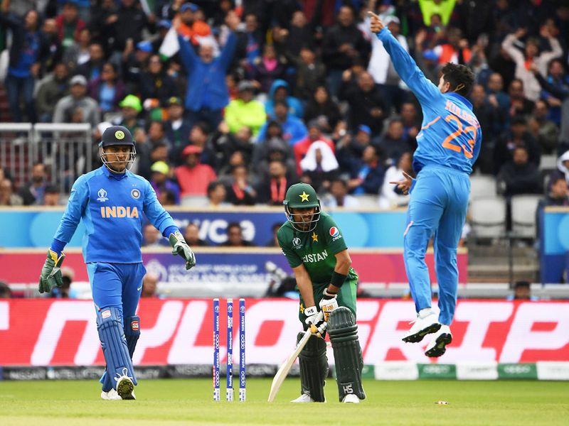 India's Kuldeep Yadav (R) leaps into the air