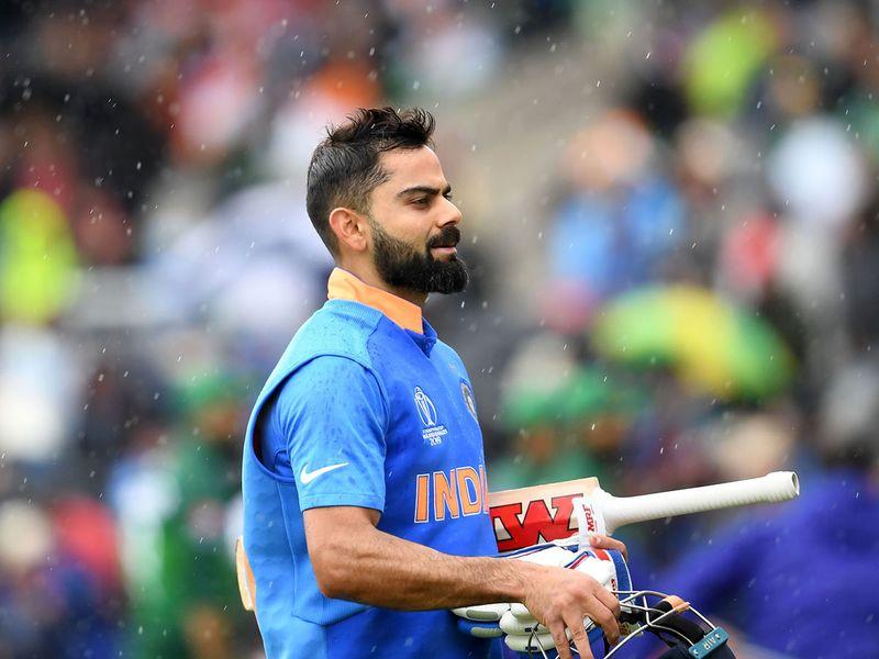 India's captain Virat Kohli walks back to the pavilion as rain stops play