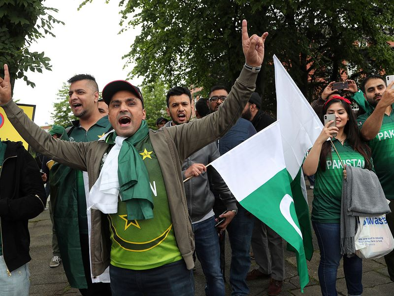 Pakistan fans dance as they arrive before the start of the match outside Old Trafford