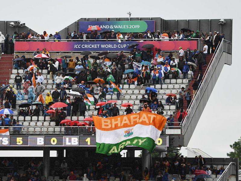 Spectators shelter as rain stops play
