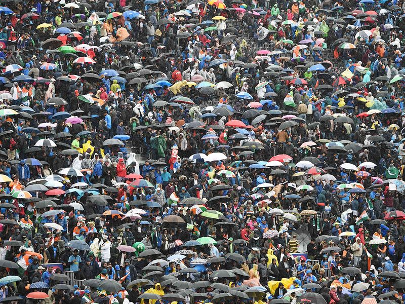 Umbrellas are up in the crowd as rain stops play