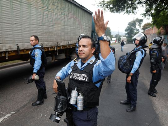 Riot police allow traffic through during a day of protests in Tegucigalpa, Honduras, Friday, June 21, 2019.