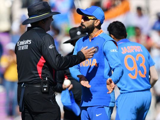 India's captain Virat Kohli (C) speaks with the umpire