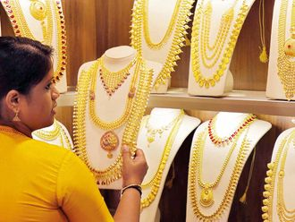 A saleswoman selects gold necklaces in a jewellery showroom in India