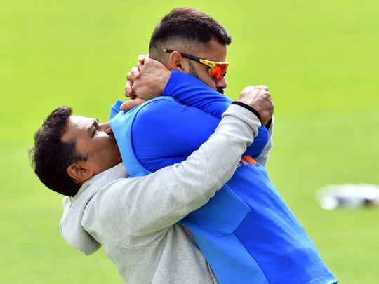 A trainer assists Virat Kohli to stretch