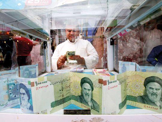 FILE: A man counts Iranian rials 012