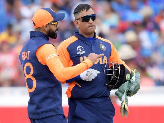 India's captain Virat Kohli ((L) speaks with MS Dhoni