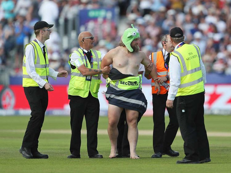 A streaker runs into the field