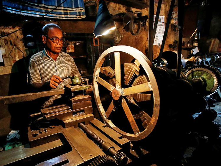 A worker operates a lathe