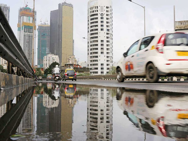 Vehicles drive past buildings under construction in Mumbai