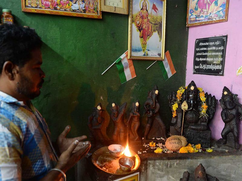 A man performs rituals to the statues of 'Ganesha'