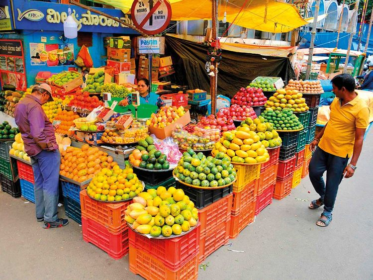 Customers at a fruit stall in Bengaluru