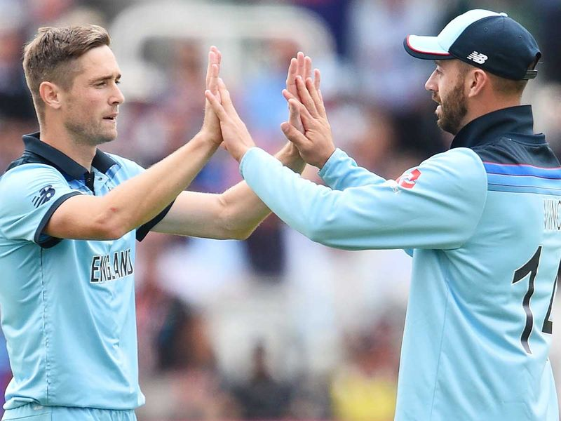 England's Chris Woakes (L) celebrates with teammate James Vince
