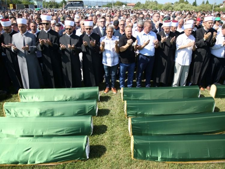 Bosnian Muslims pray in front of coffins during a mass funeral in the village of Hambarine, near Prijedor, Bosnia and Herzegovina. -091