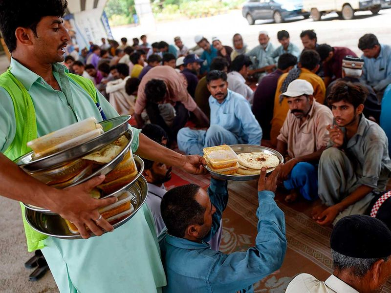 People eat charity food at a roadside in Karachi