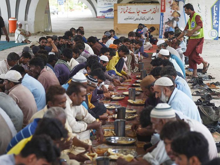 People eat charity food by a roadside in Karachi