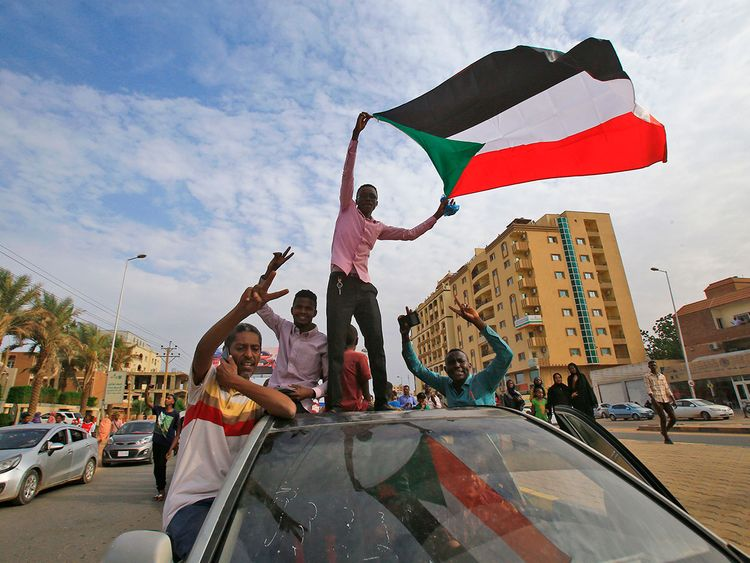 Sudanese protesters wave their national flag