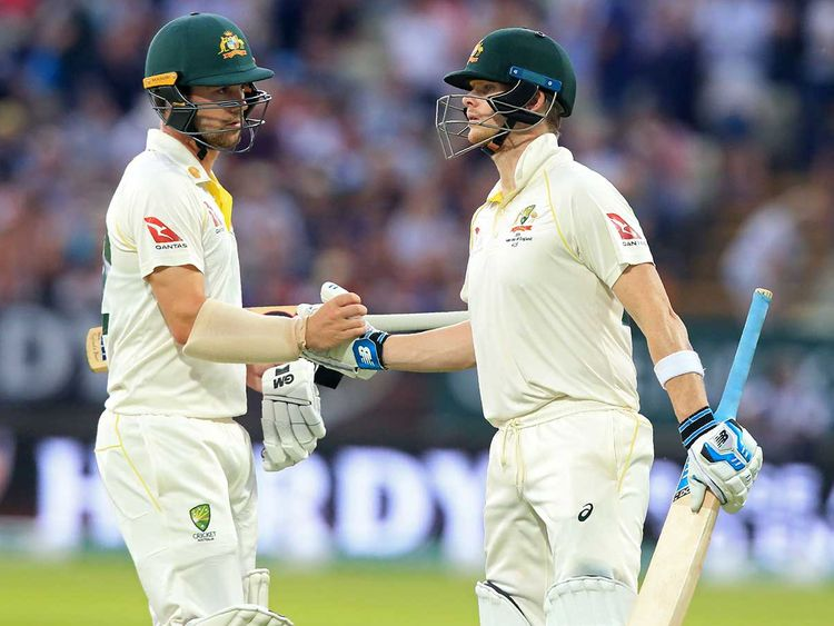 Australia's Travis Head (L) gestures to Australia's Steve Smith