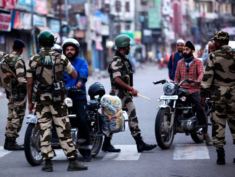 Security personnel question motorists on a street in Jammu