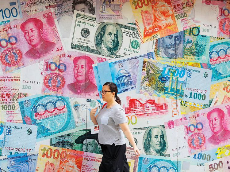 A woman walks by a money exchange in Hong Kong