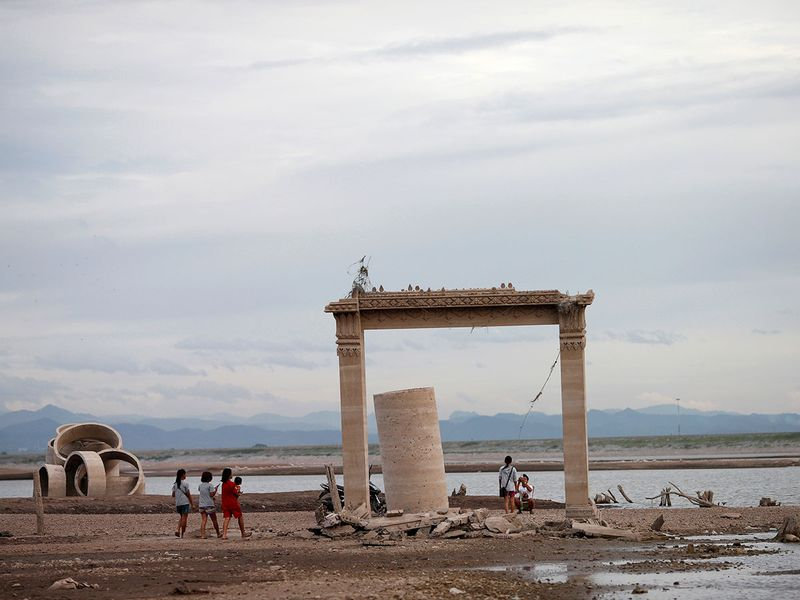 People walk through the ruins of a Buddhist temple in Lopburi