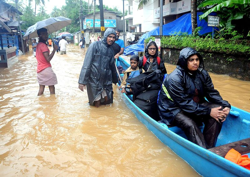 People move to safer grounds from a flood affected area in Kozhikode