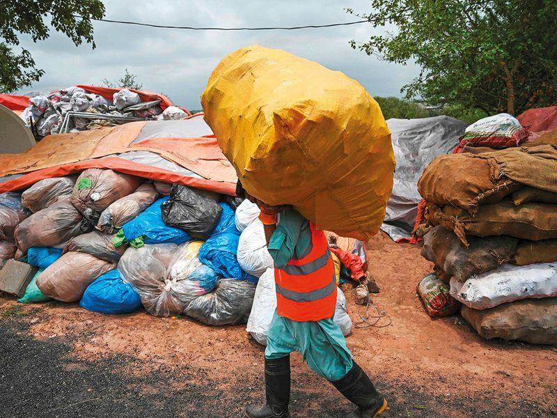 A municipal worker carries a bag of recycling items at a site in Islamabad