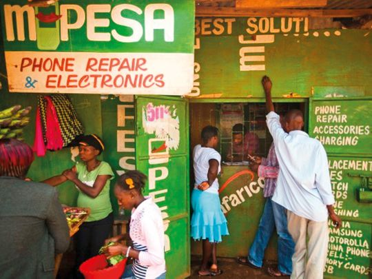 Residents transfer money using the M-Pesa banking service at a store in Nairobi